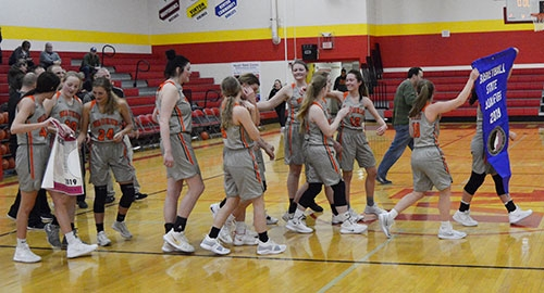 Members of the ninth-rated Waukon girls basketball team head toward their fans displaying the State Qualifier banner they were awarded after posting...